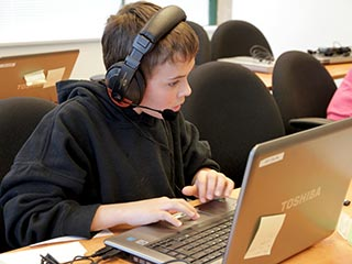 Student with headset using Dragon Naturally Speaking on a Laptop